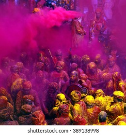 NANDGAON - MAR 22: People throw colors to each other during the Holi celebration at Krishna temple on March 22, 2013 in Nandgaon, India. Holi is the most celebrated religious festival in India.