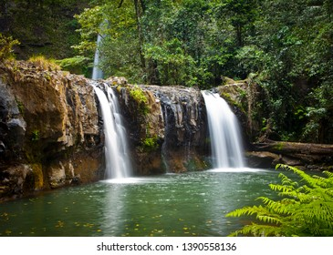 Nandroya Falls in the Wooroonooran National Park in Queensland Australia. Waterfall surrounded by lush green tropical rainforest.