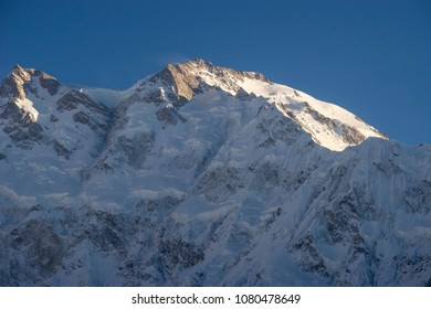 Nanga Parbat peak with sunset light bathing at top under blue clear sky, Fairy meadows, Balistan, Pakistan