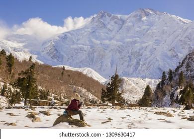 """Nanga Parbat""or Killer Mountain locally known as Diamer,the 9th highest mountain in the world Located in Diamer,Gilgit Baltistan,Pakistan.female hiker sitting at Bayal camp enjoy peak snow-covered"
