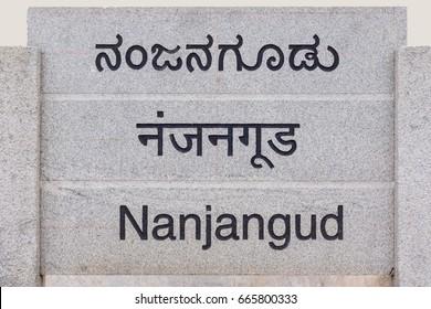 Nanjangud, India - October 26, 2013: Gray stone sign at entrance of the city showing its name in Hindi, Kannada and English languages.