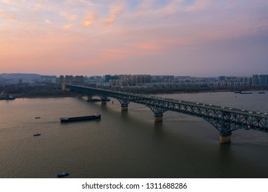 The Nanjing Yangtze river bridge and skyline of Nanjing city in the background at sunset taken with a drone.