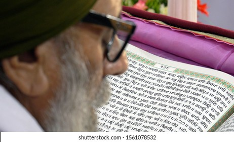 Nankana Sahib, Punjab/Pakistan - December 19, 2018: Old Sikh man reading from Sikh holy book Guru Granth Sahib, at Gurudwara Janam Asthan, in Nankana Sahib.