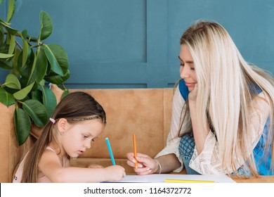 nanny and child artful leisure. babysitter and little girl drawing together. preschool education and kids upbringing.