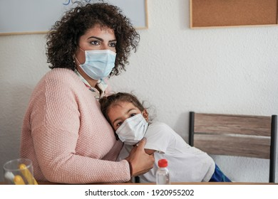 Nanny and little child wearing surgical face masks at home indoor - Coronavirus outbreak and home schooling concept
