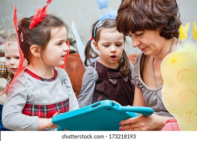 Nanny playing with children and teaching them with children`s tablet