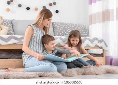Nanny reading book to little children at home