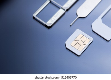 nano sim card, sim card adaptor, sim card tray and eject tool on black screen glass background