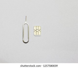 Nano sim card and Eject tool on white paper background