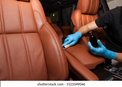 nano-ceramic coating on leather of the car seat brown upholstery by a worker in blue gloves with a sponge and bottle