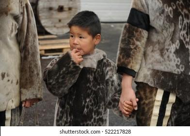 NANORTALIK, GREENLAND - SEPTEMBER, 2013: Inuit eskimo boy holding his mother's arm