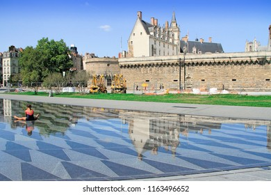 NANTES, France – August, 18, 2018 : Girl sitting at the water mirror fountain with the View on the castle of Dukes of Brittany in Nantes city in France