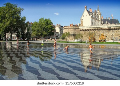 NANTES, FRANCE – August, 18, 2018 : View on the castle of Dukes of Brittany with water mirror fountain and tourists in Nantes city in France