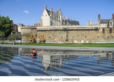 NANTES, France – August, 18, 2018 : Girl sitting in the water mirror fountain with the View on the castle of Dukes of Brittany in Nantes city in France