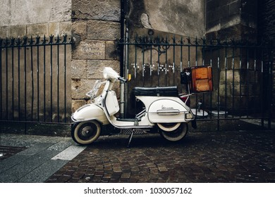 NANTES, FRANCE - CIRCA JANUARY 2018: A vintage Vespa scooter parked in the street by a rainy day.