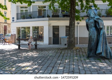 Nantes, France - May 12, 2019: One elderly woman sitting on the bench under green trees near statue of Anne de Bretagne Queen of France. Nantes France