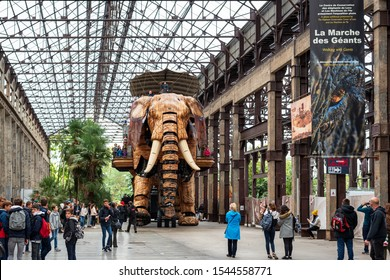 """NANTES, FRANCE - OCTOBER 8, 2019: The Great Elephant walking with passengers aboard, one of the many attactions of """"The Machines of the Isle of Nantes"""", an artistic, touristic and cultural project."""