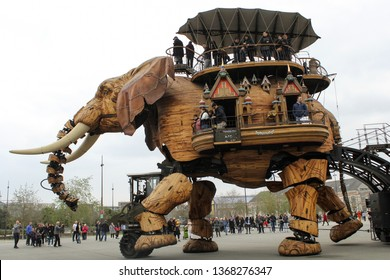 NANTES, FRANCE-MAR. 24, 2019:  The giant mechanical elephant of Les Machines de l'lili walks about with dozens of visitors on his back and inside and many more surrounding it clicking photos.