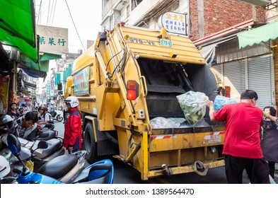 Nantou, Taiwan - April 8th, 2019:yellow garbage truck for collects garbages in the traditional marketplace at Puli township, Nantou, Taiwan, Asia