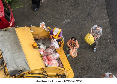 Nantou, Taiwan - Jun 14th, 2019:yellow garbage truck for collects garbages in the small lanes at Puli township, Nantou, Taiwan, Asia