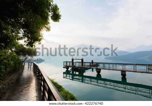 Nantou, Taiwan - May 09, 2016 : Tourist boats docking and sidewalk in peachful morning at Shuishe Pier, Sun Moon Lake, Taiwan.