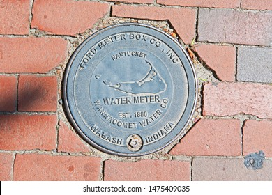 Nantucket, Massachusetts/USA - August 9 2019: a cast iron cover for a water meter or switch is custom made in Wabash Indiana for the island of Nantucket and set into the sidewalk.