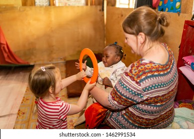 Nanyuki, Laikipia county, Kenya – June 10th, 2019: English charity worker and young daughter showing a Kenyan nursery toddler a frisbee that was part of a large toy donation supplied by Jalia charity.