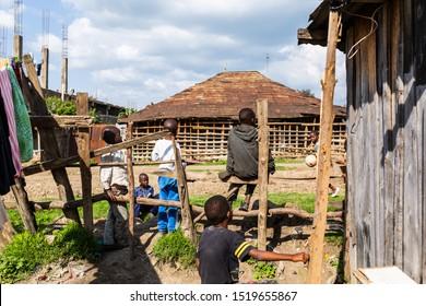 Nanyuki, Laikipia county, Kenya – June 19th, 2019: Impoverished Kenyan children sitting on-side of stone road in Kenyan suburb.