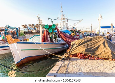 Naoussa Village: July 10th .  Colourful Greek fishing boats and fishermen in Port of Nausa . Paros Island , Naoussa July 10th 2017, Greece.