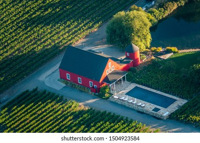 Napa, California - September 8, 2019: A red barn style house with pool is viewed from above among the vineyards of Napa Valley during a hot air balloon ride.