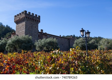 NAPA VALLEY, CALIFORNIA - November 8, 2016 : Castello di Amorosa's turret rising above large olive trees and fall grape vine leaves on November 8, 2016 in Napa Valley, California.