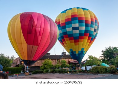 Napa Valley, California - September 8, 2019; Two hot air balloons prepare for lift off in the early morning in Napa Valley.