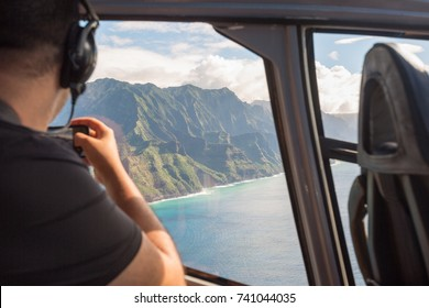 Napali coast from a helicopter with a tourist taking pictures - Kauai, Hawaii