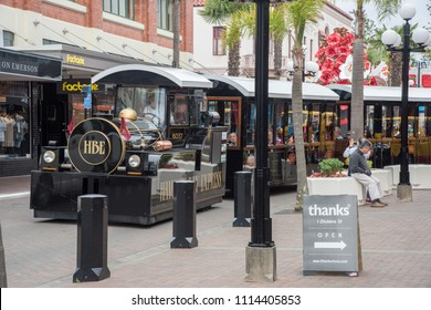 Napier, Hawke's Bay/New Zealand-December 15,2016: Hawke's Bay Express touring train with tourists and storefronts in outdoor mall in Napier, New Zealand