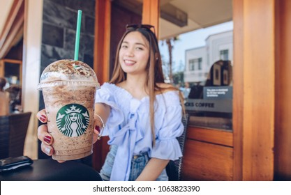 Napier, New Zealand -April/01/2018- : Asian women holding and showing her cup of Starbucks Frappuccino in Napier Starbucks coffee shop.
