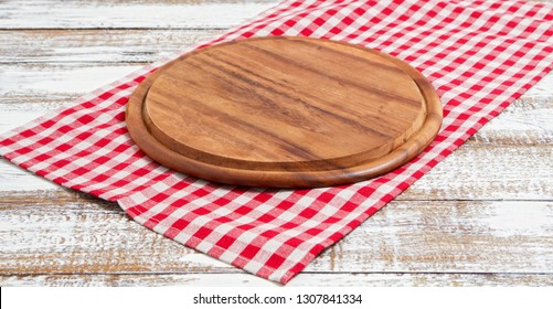 Napkin and board for pizza on wooden desk closeup, tablecloth. Canvas, dish towels on white wooden table background top view mock up. Selective focus