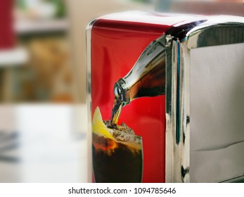 Napkin dispenser with a picture on one side, a beverage bottle pours a drink into a glass in which ice cubes and a lemon slice is inside. Background of image bright red, background image of Bookeh.