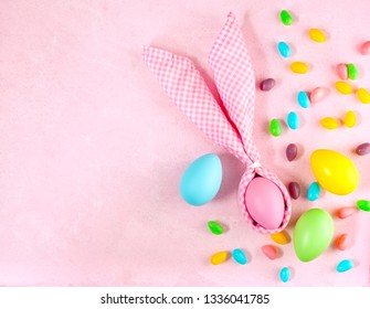 Napkin Easter Bunny, decoration eggs and Easter candy on pink background, copy space
