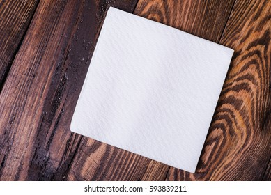 Napkin isolated on wooden background. Kitchen paper serviette. Clean food towel in restaurant. Single square shape object. Blank tablecloth on table. Domestic, cafe cloth.