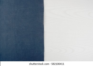 Napkin from left side wooden table. White blue background. Blue woven linen fabric texture / white wood texture.