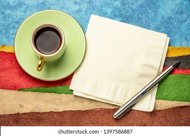 napkin, pen and a cup of coffee against abstract landscape created with sheets of textured colorful handmade paper