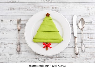 Napkin in the shape of a Christmas tree with anise star and cinnamon stick as a  tree trunk on plate, top view