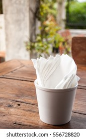 Napkin or tissue paper in a cup, on a wooden table