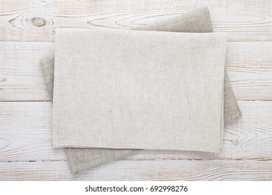 Napkin white. Stack of grey dish towels on white wooden table background top view closeup