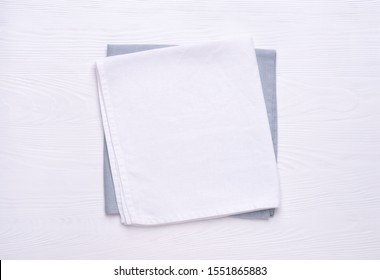 Napkins on white wooden table top. Mock up for design. Top view