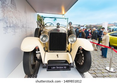 Naplavka, Stare Mesto, Praha, CZ - SEP 1, 2018:  Nostalgia Laurin and Klement Skoda 110 beige classic car watched by elderly lady at public Prague Vltava River Drift Banks Auto Show (Auta na Naplavce)