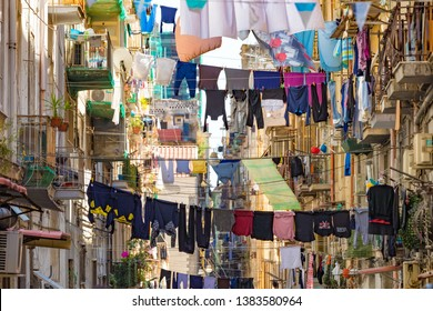 Naples, Campania, Italy - April 19, 2019: Various clothes are dried after washing on ropes stretched between balconies on narrow street of Naples, Italy