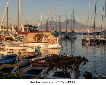 Naples, Campania, Italy. Seaside and vesuvius volcano at sunset. Harbour and fishing boats