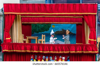 Naples, Campania region, Italy, May 5, 2017: Puppet show with Punch and man with checkered suit. Two characters playing in street puppet theater with red curtains. Pulcinella in traditional black mask