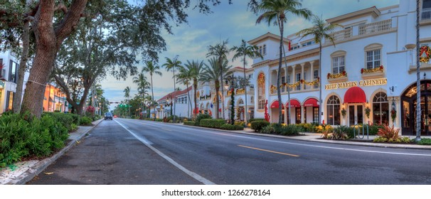Naples, Florida, USA – December 22, 2018: Christmas lights as day breaks over the shops along 5th Street in Old Naples, Florida.